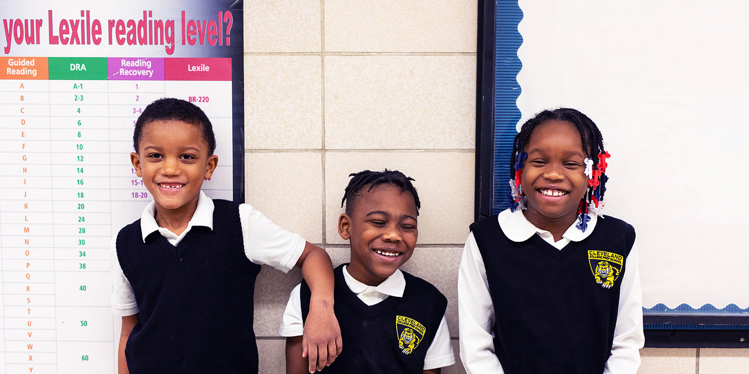 Three smiling students standing next to each other.