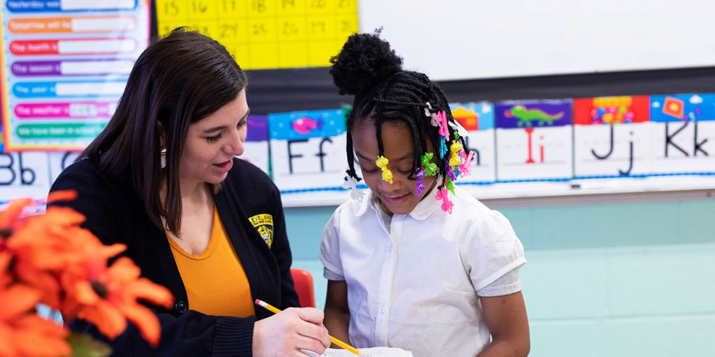Teacher holding pencil and showing student work on paper.