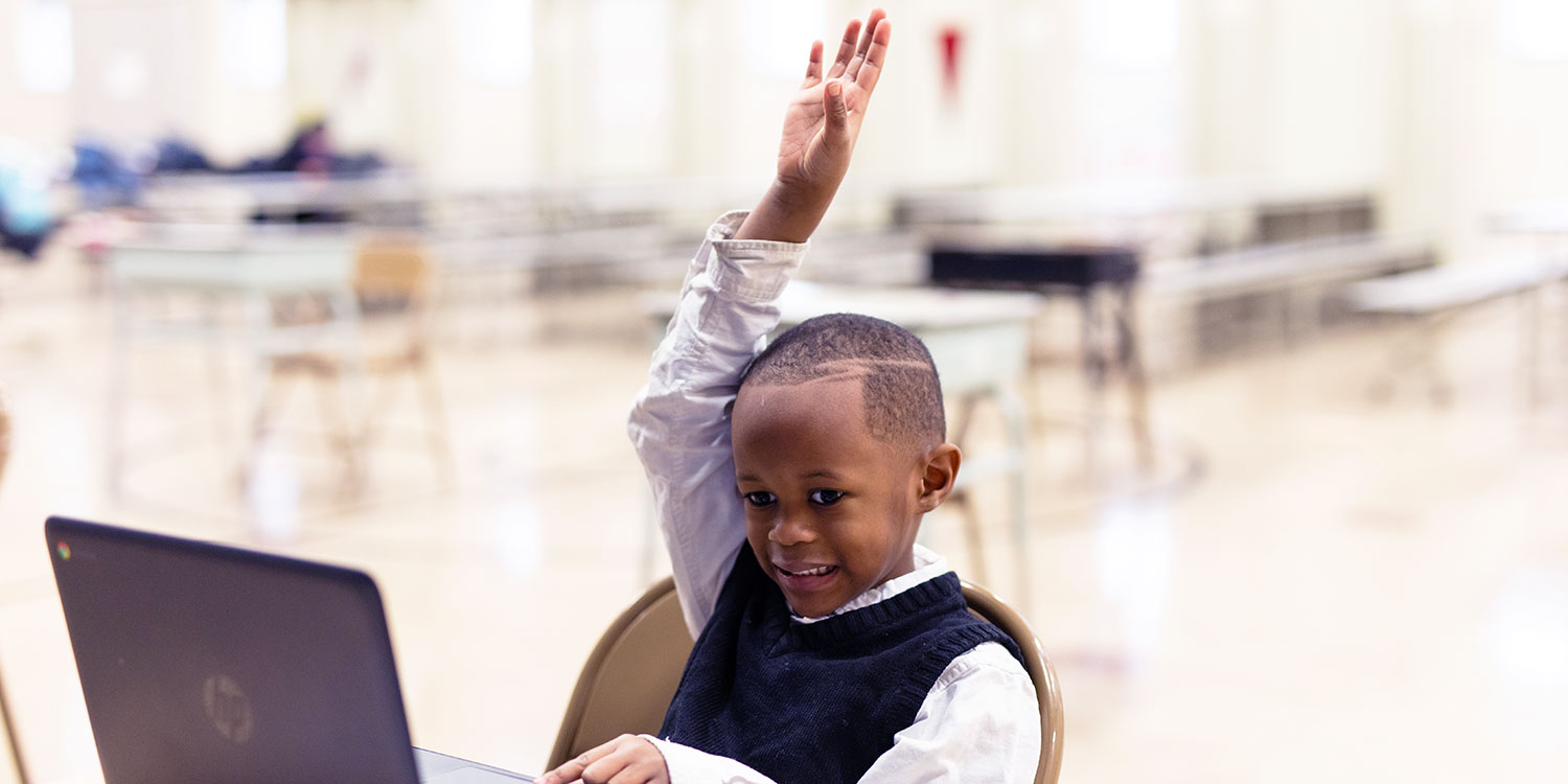 Student sitting at desk with raised hand.
