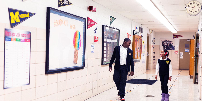 Smiling students walking down school hallway.